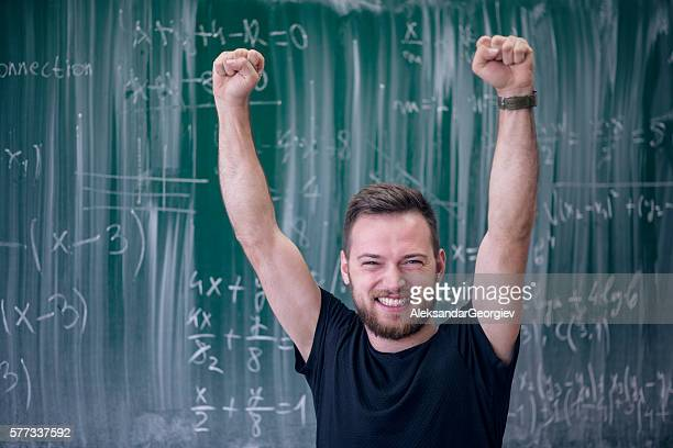 Excited Smiling Student With Raised Arms in Front of Blackboard