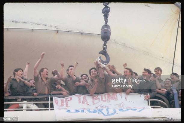 Excited soldiers reaching for Army wife's bra passed by crane fr. Dock to QE2, before sailing to Falklands