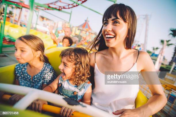 Excited son and daughter with mother on roller coaster ride