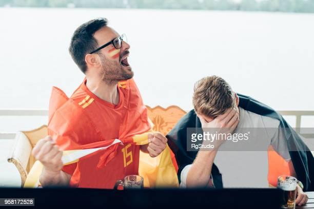 spanische fußball-enthusiasten spiel mit enttäuscht deutsche team unterstützer beobachten begeistert - weltmeisterschaft stock-fotos und bilder
