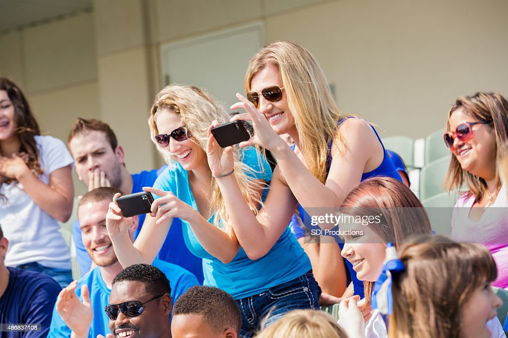 Excited sports fans taking photos during sporting event in stadium : Stock Photo