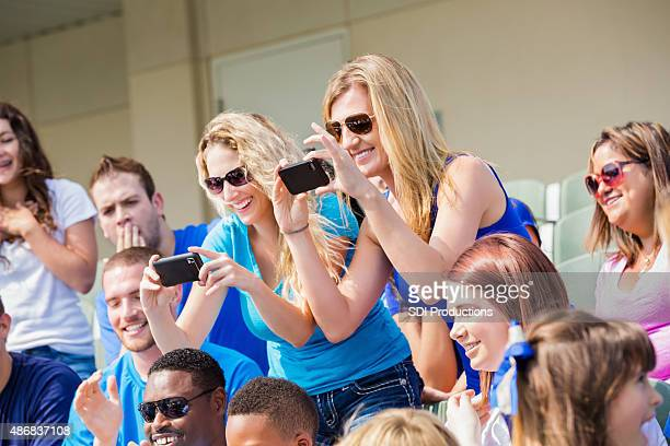 Excited sports fans taking photos during sporting event in stadium