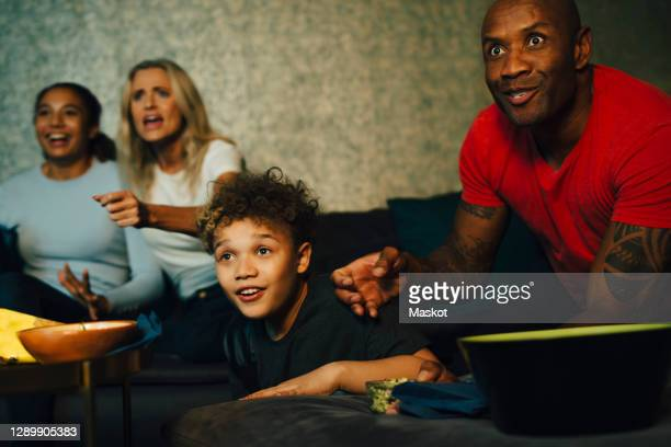 excited sports fans watching tv together at night - television stock pictures, royalty-free photos & images