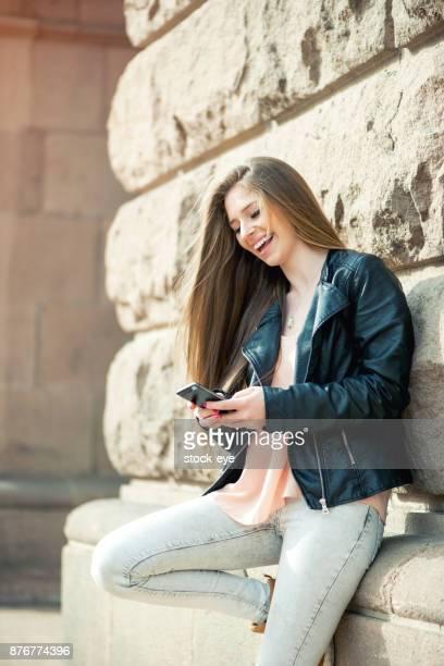 Begeistert Schüler lesen Nachrichten auf einem Smartphone