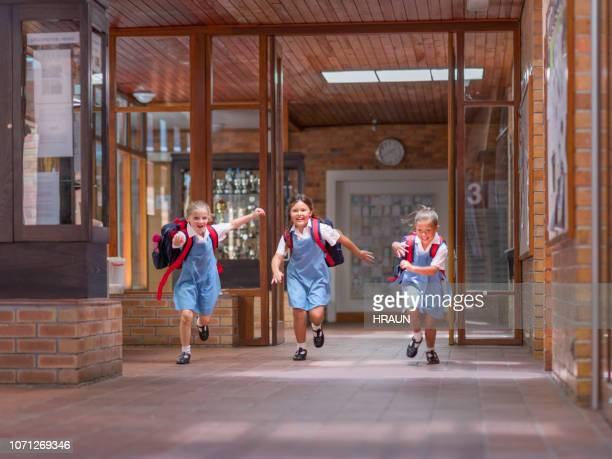 Estudiantes entusiasmados corriendo hacia la entrada