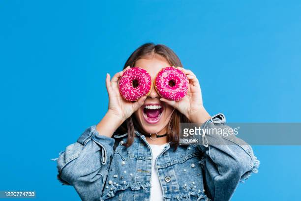 excited teenage girl covering eyes with donuts - sweet food stock pictures, royalty-free photos & images