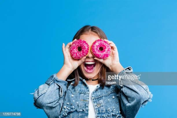 ドーナツで目を覆う興奮した十代の少女 - ドーナツ ストックフォトと画像