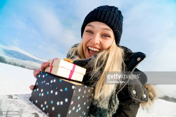 Excited Teenaged Woman With Gifts in Hands Outdoors on Snow