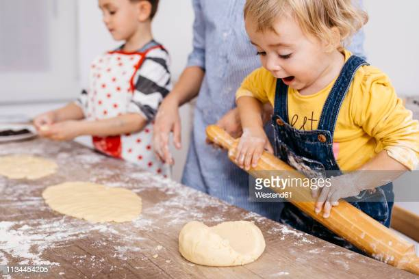 excited toddler girl rolling out dough with wooden rolling pin - guardare verso il basso foto e immagini stock