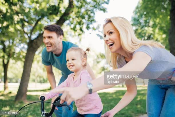 Heureux bambin monté sur un vélo avec les parents