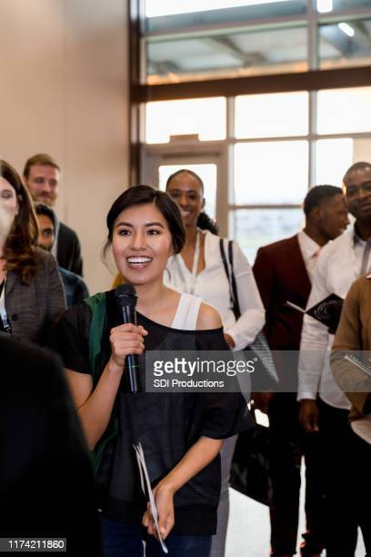 excited woman asks a question during business conference - riunione municipale foto e immagini stock
