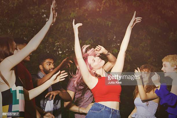 excited woman dancing with friends at yard during party - india summer fotografías e imágenes de stock