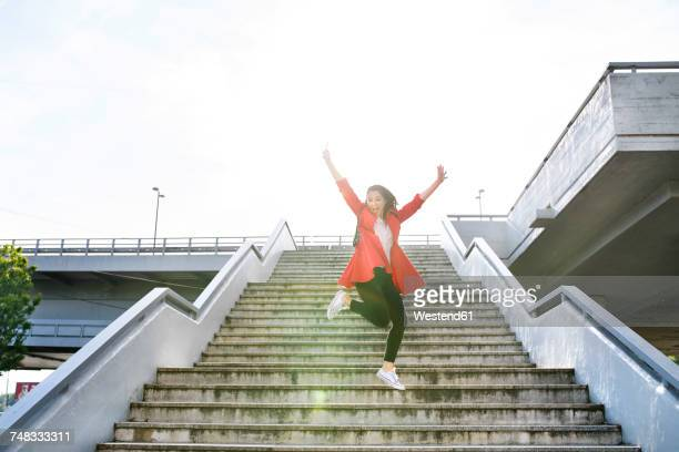 Excited woman in the city jumping on stairs
