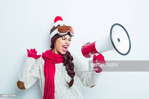 Excited woman in winter outfit, shouting into megaphone