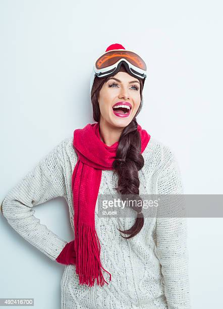 Excited woman in winter outfit, wearing knitt cap and goggle
