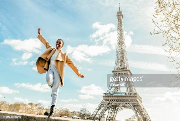 excited woman jumping from retaining wall with eiffel tower in background, paris, france - paris france foto e immagini stock