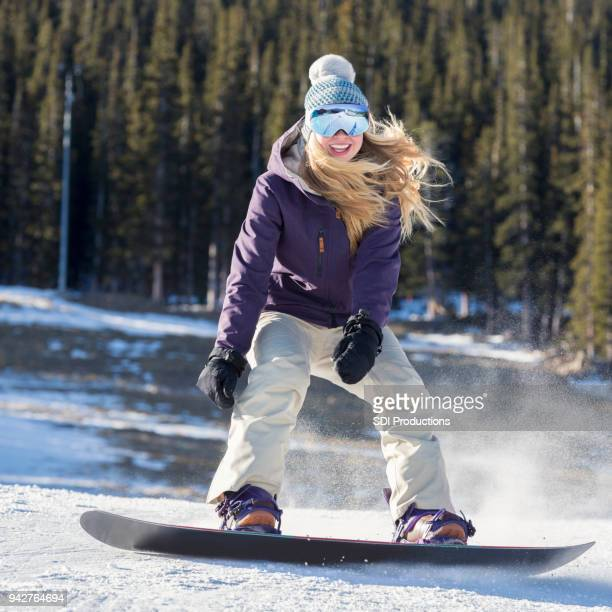 excited woman on snowboard - ski pants stock pictures, royalty-free photos & images