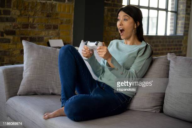 excited woman playing video games at home - control stock pictures, royalty-free photos & images