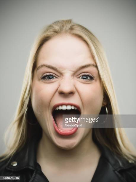 Excited woman screaming against gray background