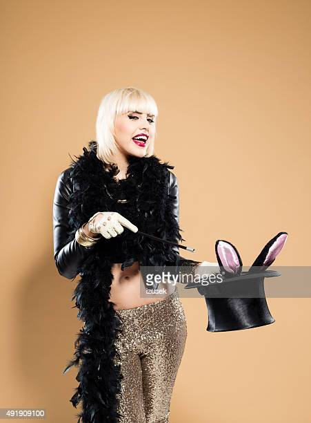 Excited woman wearing feather boa holding cylinder hat