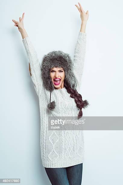 Excité femme crier en fourrure portant la casquette en relief les bras