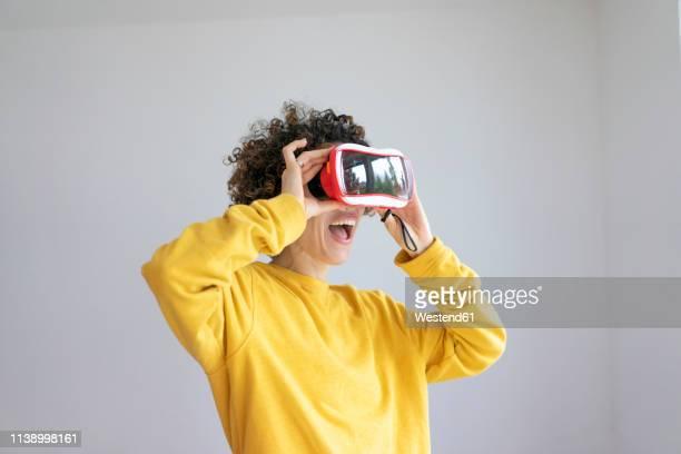 excited woman wearing vr glasses - virtuelle realität stock-fotos und bilder