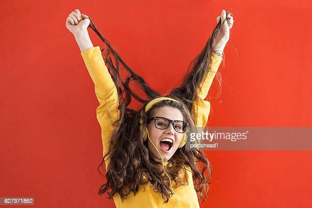 Excited woman with yellow headphones listening music, red background