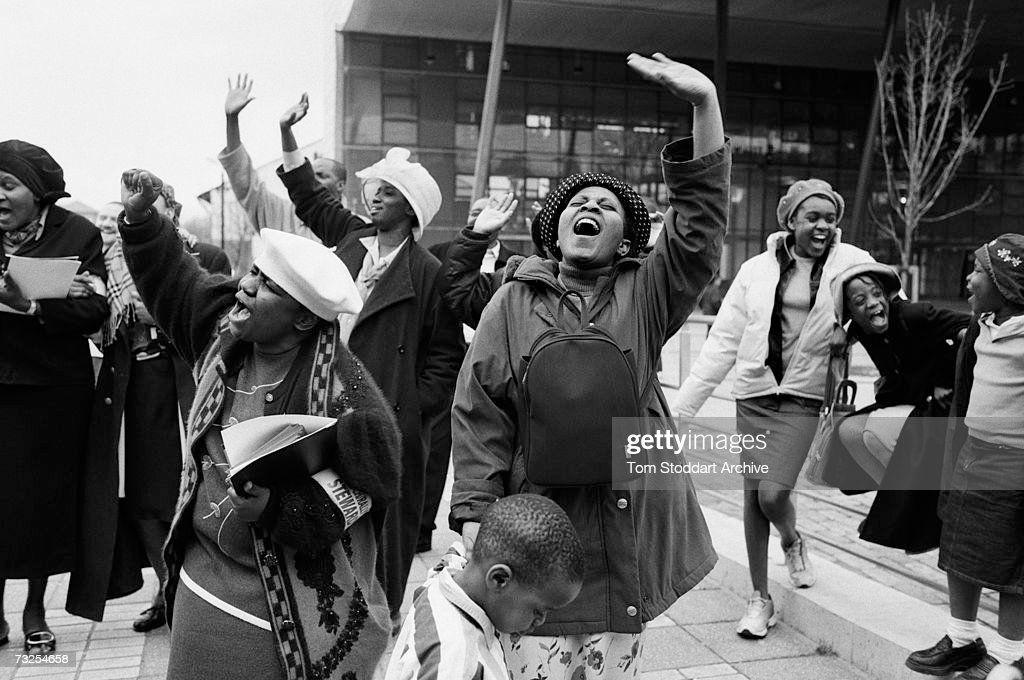 Excited women wave to friends and supporters during an anti-racism demonstration in Brixton, south London, May 2001.