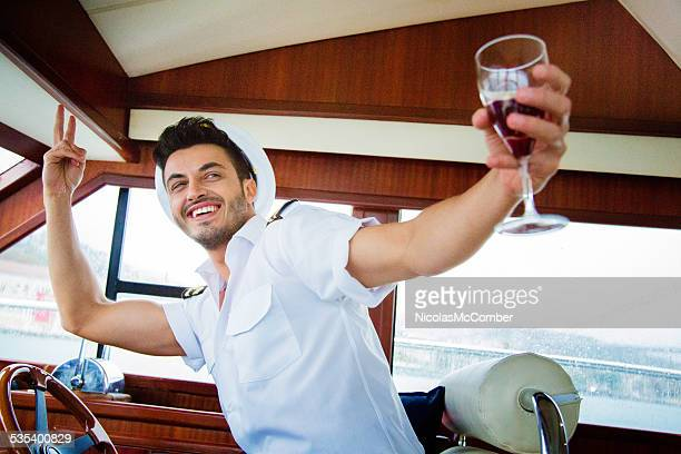 Excited yacht captain toasts with red wine at party