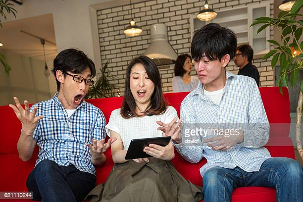 Excited Young Adult Japanese Family Laughing at Tablet Computer