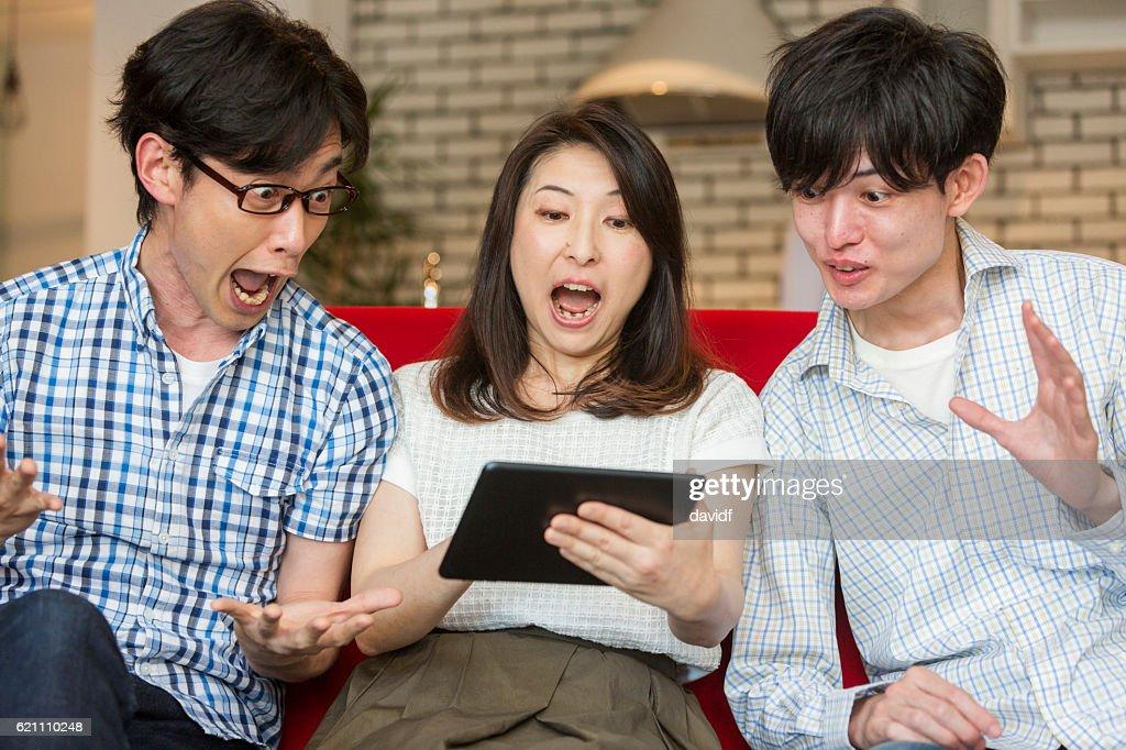 タブレットコンピュータで笑う興奮した若い大人の日本人家族 : ストックフォト