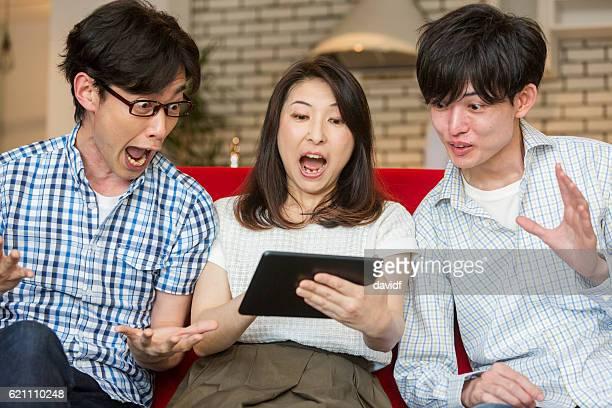 タブレットコンピュータで笑う興奮した若い大人の日本人家族 - サプライズ ストックフォトと画像