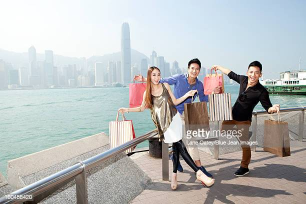 Excited young adults with shopping bags in Victoria Harbor, Hong Kong