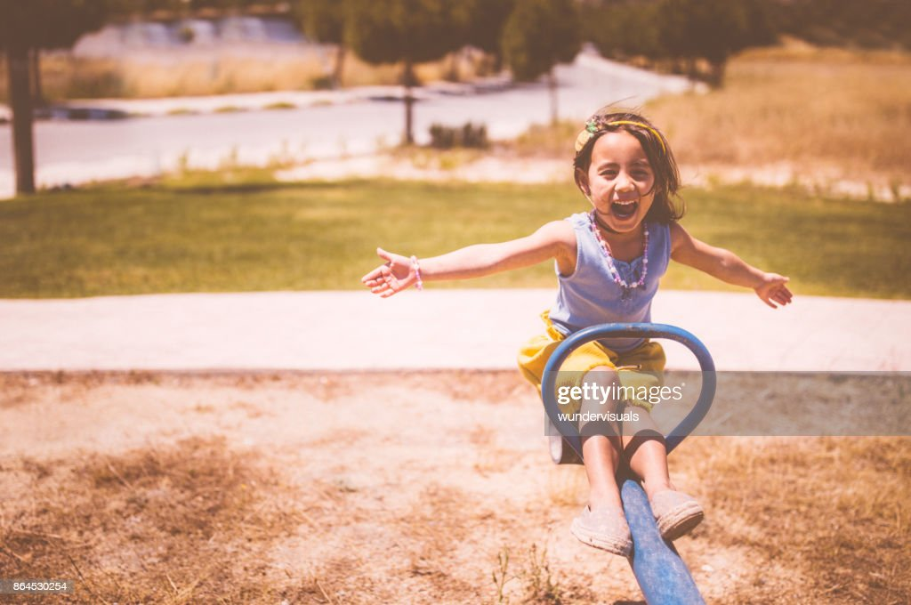 Excited young Asian girl having fun at the playground : Stock Photo