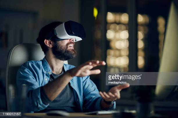 excited young bearded man sitting in front of computer and gesturing hands while testing new app via vr device - simulatore di realtà virtuale foto e immagini stock