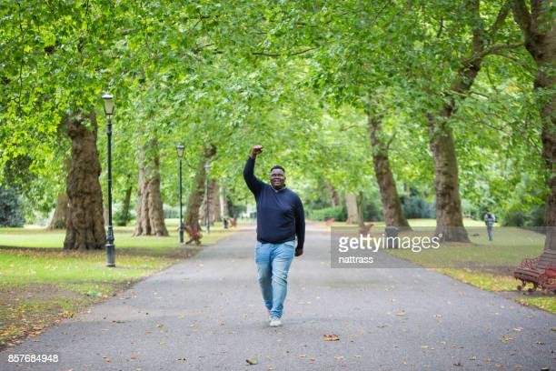 excited young black male punches the air - battersea park stock photos and pictures