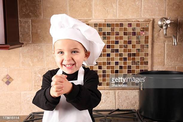 Contente jovem rapaz brincando com um papel de chefe de cozinha