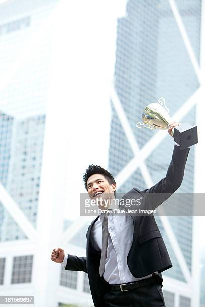 Excited young businessman jumping with a trophy in hand, Hong Kong