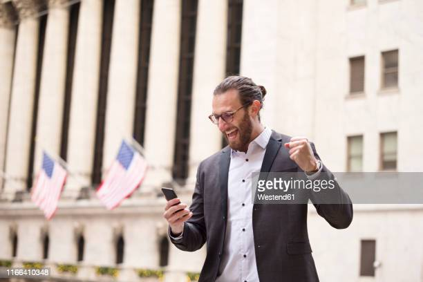 excited young businessman looking at cell phone in front of stock exchange, new york city, usa - bull market stock pictures, royalty-free photos & images