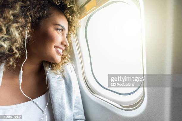 Excited young businesswoman enjoys window seat during air travel