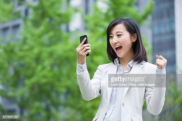 Excited young businesswoman with mobile phone