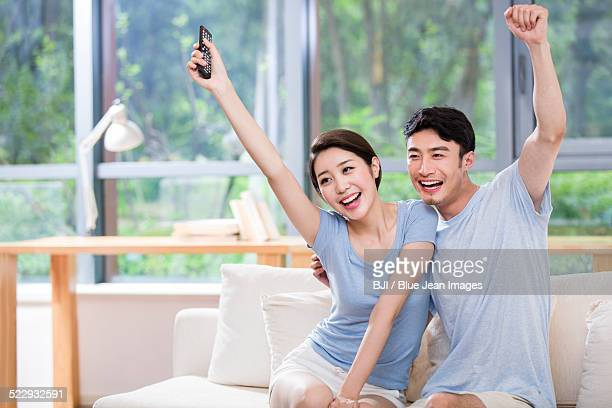 Excited young couple watching TV