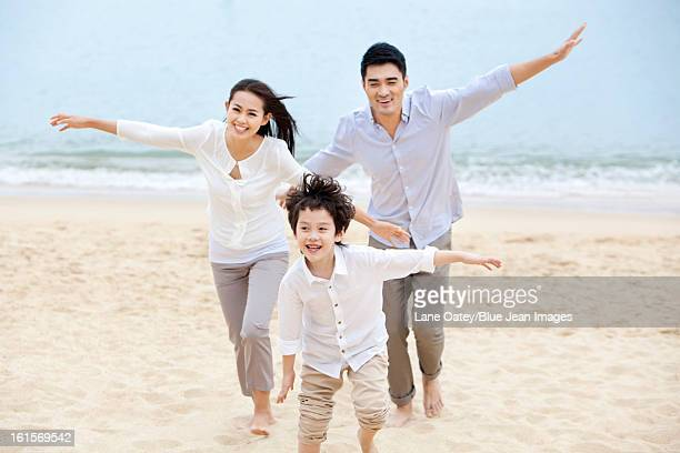 Excited young family pretending to be flying on the beach of Repulse Bay, Hong Kong