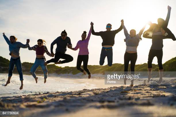 Excited young friends jumping at beach