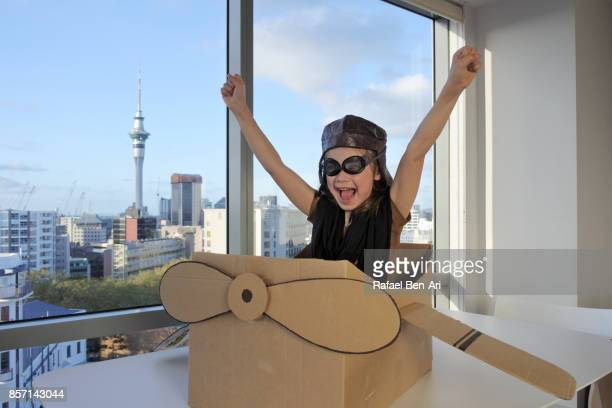 excited young girl flying a cardboard airplane above city - rafael ben ari fotografías e imágenes de stock