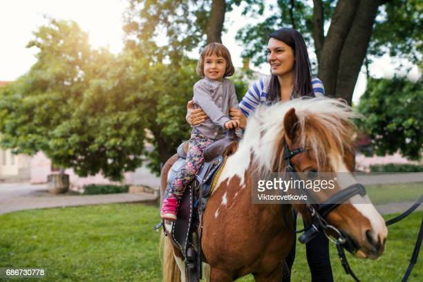 Excited Young Girl Taking a Pony Ride