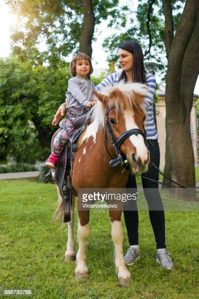 upphetsad ung flicka tar en ridtur på en ponny - pony play bildbanksfoton och bilder
