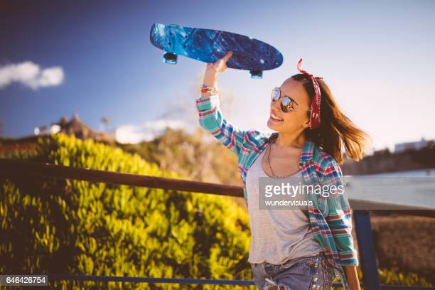 Excited young hipster girl ready to meet friends for skateboarding