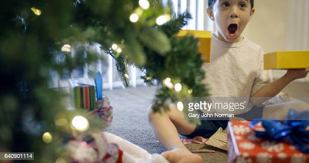 excited, young hispanic boy opening gifts under christmas tree. - southern christmas stock pictures, royalty-free photos & images