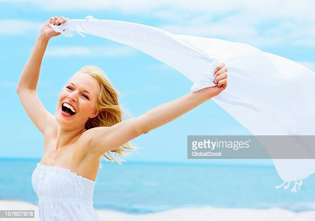 excited young lady holding a sarong against the wind - shawl stock photos and pictures